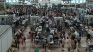 Denver International Airport security lines and TSA workers screening travelers in the main terminal