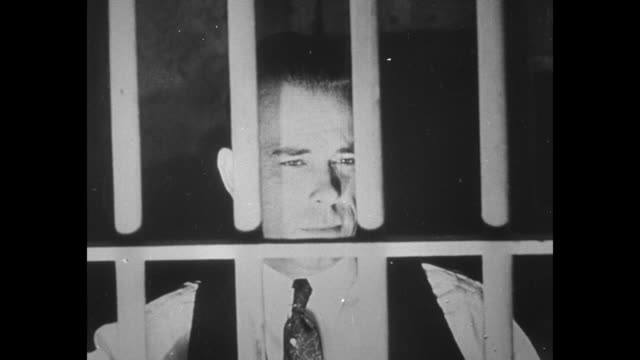 EXT Department of Justice building with eagle insignia / gangster John Dillinger clean shaven looks out through bars of jail cell during...