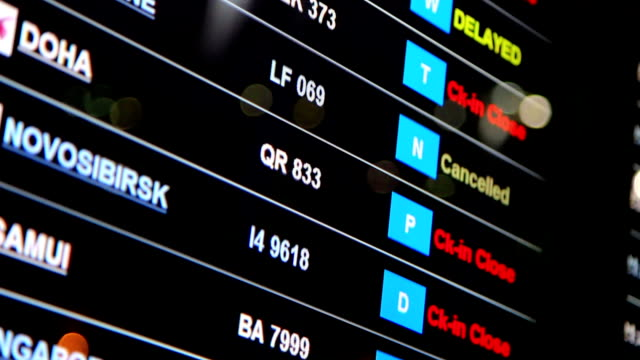Departures board at airport terminal showing flights.