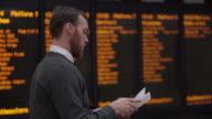 Departures board man documents.