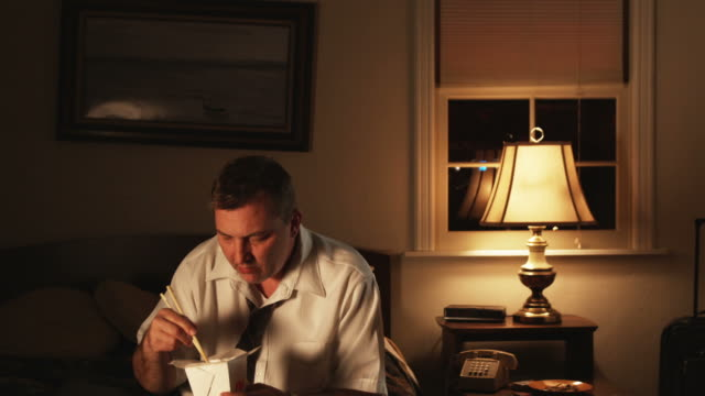 depressed man eating Chinese food and watching TV in a motel room