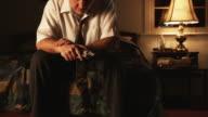 depressed man sitting and holding a handgun