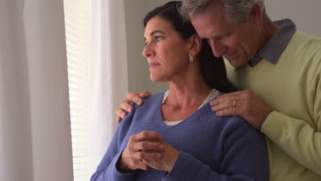 Depressed senior wife standing by window with husband