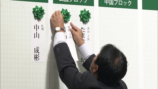 Deputy president of the Hope party Shinji Tarutoko putting flowers on a chart of indicating candidates winning a seat after the general election of...