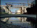 Derelict-looking Bulgarian factory reflected in puddle in pothole