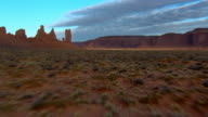 Desert brush grows amongst rock formations in Monument Valley, Arizona.