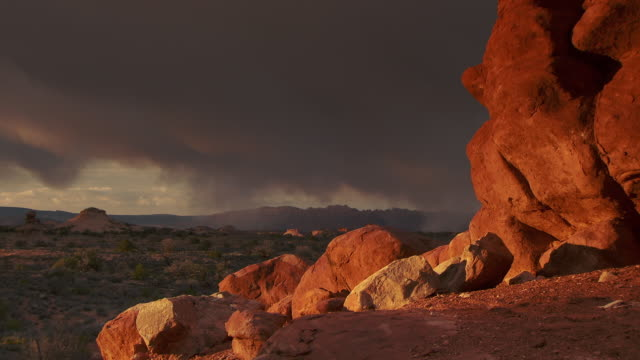 Desert scene with red rock cliffs and distant storm clouds
