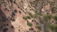 Desert shrubs dot the scrubland of a canyon in Utah. Available in HD