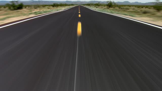 A deserted road cuts through the desert, leading toward a mountain.