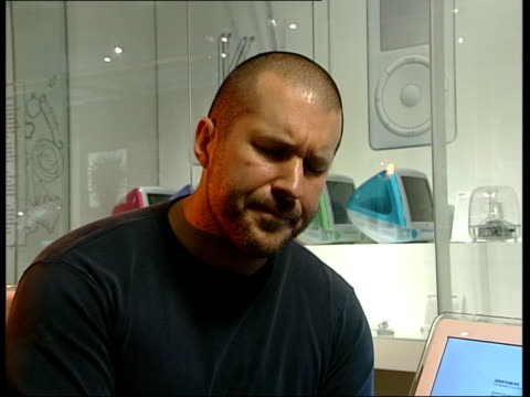 BV Visitor looking at display of Apple computers MS Line of different coloured Apple computers CMS Apple logo ZOOM IN Jonathan Ive interview SOT 10...