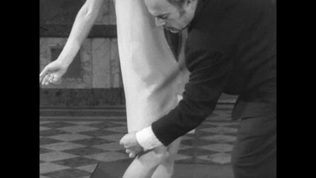 Designer Jacques Esterel shows designs in Paris / models wear pants under dresses / Esteral adjusts a model's outfit / CU watch embedded in model's...