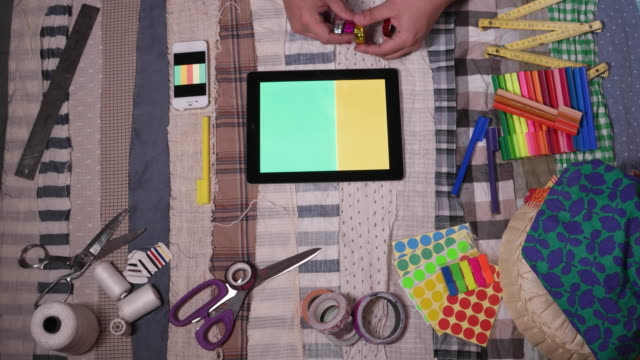 A designer using technology, tablets and phone to select colours