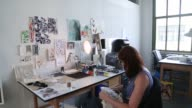 Designers work on projects at the West Elm Makers Studio in Brooklyn US on Tuesday July 7 2015 Shots Female employees sit at workstations painting...
