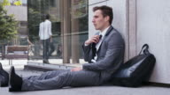Desperate businessman sitting on the street