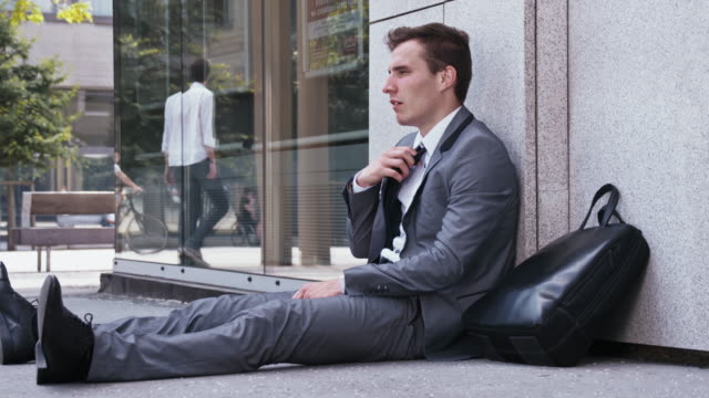 Desperate businessman sitting on the street