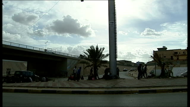 The African Exodus Migrants caught in lawless Libya Various of men sitting together on floor and standing leaning against wall Khaled Ali interview...