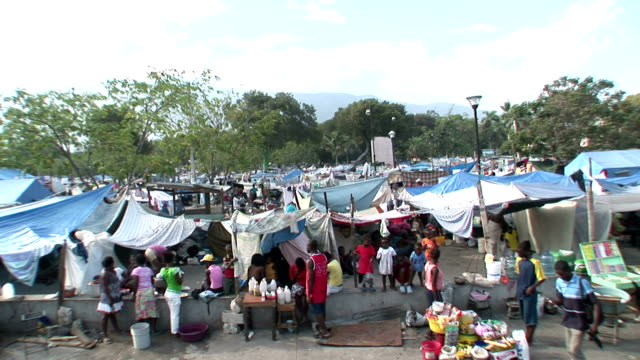 Destroyed buildings rubble / makeshift refugee camp tents / CU of bed in tent made with tires and blankets Living conditions in Haiti after...