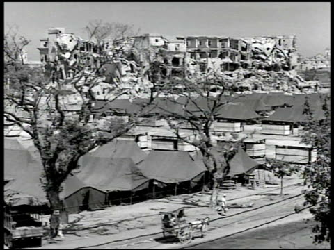 Destroyed city rubble canal WS Rows of tents ruined building BG WS Deserted buildings VS Trucks Philippines crowded on street Quiapo Church BG VS...