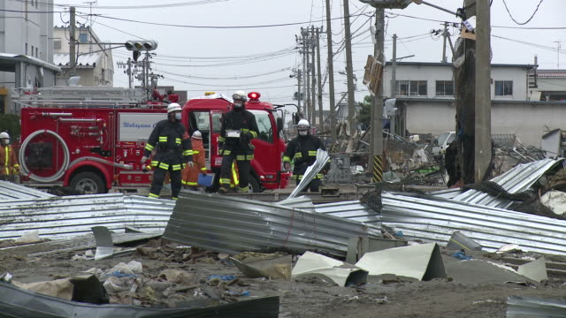 Destruction caused by tsunami after magnitude 9 Tohoku earthquake, north east Japan, March 2011. Fire crews walk over debris in Ishinomaki City,  Miyagi Prefecture