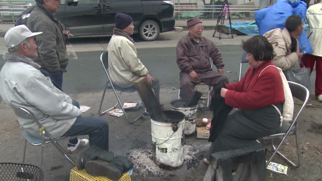 Destruction caused by tsunami after magnitude 9 Tohoku earthquake, north east Japan, March 2011. Elderly survirors sit around fire on street to keep warm after tsunami in Ishinomaki
