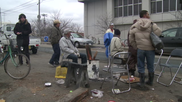 Destruction caused by tsunami after magnitude 9 Tohoku earthquake, north east Japan, March 2011. Elderly survirors sit around fire on street to keep warm after tsunami in Ishinomaki,  Miyagi Prefecture