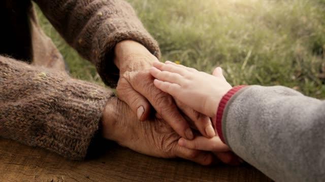 EEN HELPENDE HAND. Detail van een kind handen houden de handen van de Senior vrouw