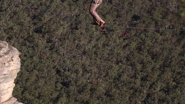 Detail of a person walking on a highline rigged between cliffs at Corroboree Walls in Mount Victoria on March 6 2015 in the Blue Mountains Australia...