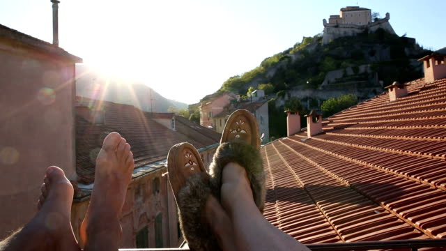 Detail of couple's feet relaxing on medieval rooftop terrace