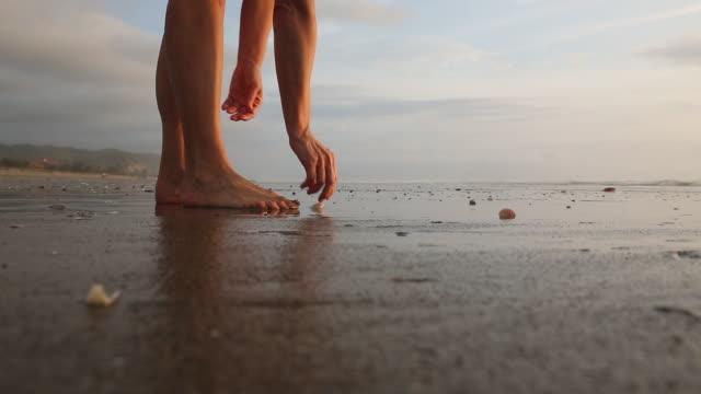 Detail of woman beachcombing on tidal flat, at sunrise