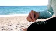 Detail of woman sifting through sandy beach, finding gems
