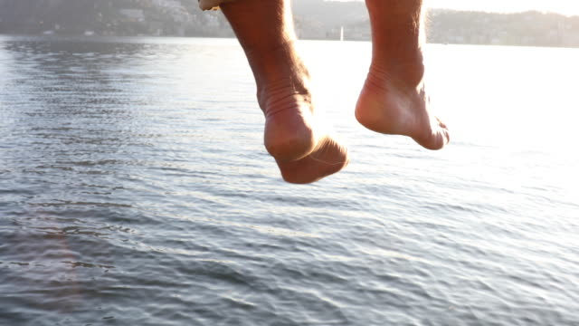 Details of man's legs and bare feet, hanging above lake