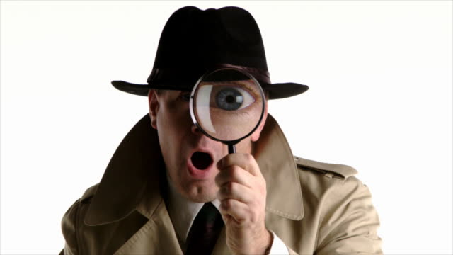 Detective looks through magnifying glass