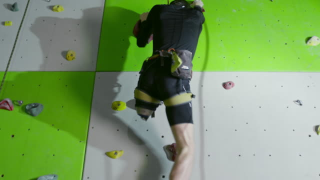Determined amputee man going up on climbing wall