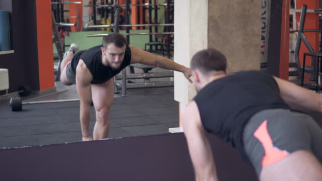 Determined athlete performing workout with dumbbell at gym