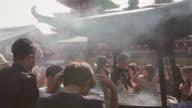 MS Devotees waft incence smoke over themselves at Sensoji Temple, Tokyo / Tokyo, Japan