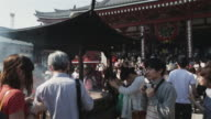 WS Devotees waft incence smoke over themselves at Sensoji Temple, Tokyo / Tokyo, Japan