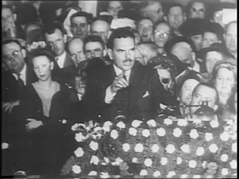 Dewey and wife Frances ride in car surrounded by people / crowd lines street / Dewey on platform in front of large crowd / Dewey gives speech at...