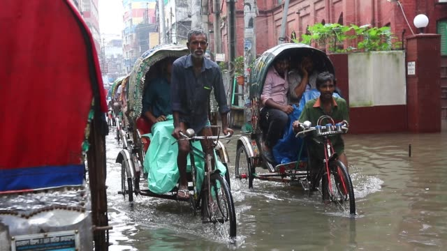 Dhaka Bangladesh 05 July 2017 Rickshaw pullers make two lanes for passing through a road in Old Dhaka Heavy monsoon rainwater leads to severe...