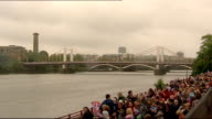 1200 1230 ENGLAND London River Thames EXT Tug boat along River Thames / Crowds lined up along River waving flags with Chelsea Bridge in background /...