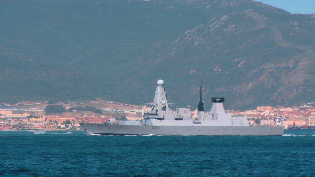 MS TS HMS Diamond navy ship moving at bay with small boats / Gibraltar