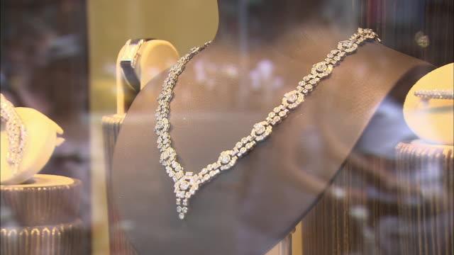 CU, R/F, Diamond necklace on window display reflecting busy street, New York City, New York, USA