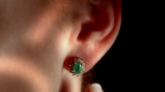 CU TD diamond studded ear ring with green emerald stone on female ear as her finger touches it / Los Angeles, California, USA