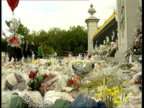 Queen denies pressure cC5N ITN ENGLAND London Buckingham Palace GVS People putting flowers down at palace gates i/c