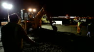 WS Digger and men with shovels digging up the old road on construction site at night, Cape Town, South Africa