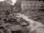 A digger attempts to move rubble in the village of Lynmouth following the flooding disaster