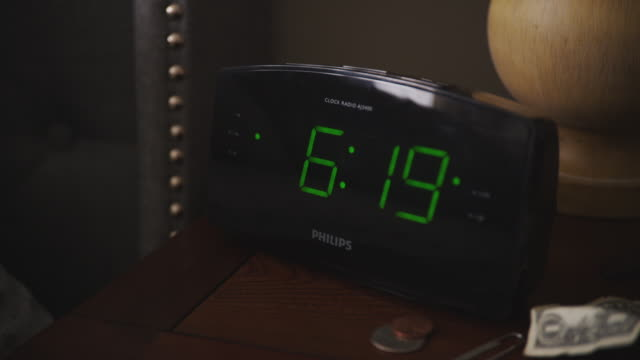 Digital alarm clock is shut off at 6:20 a.m. by a woman's hand.