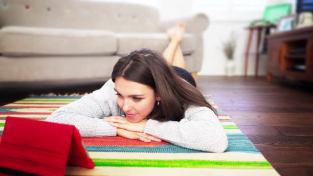 Digital tablet, watching TV. Young woman.