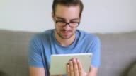 Digital tablet, young man with glasses and beard.