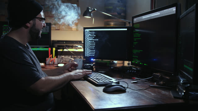 Digital threat by male cyber criminal computer hacker typing computer code while trying to break into a computer network during night – he smokes a cigarette and enters the frame in the end.
