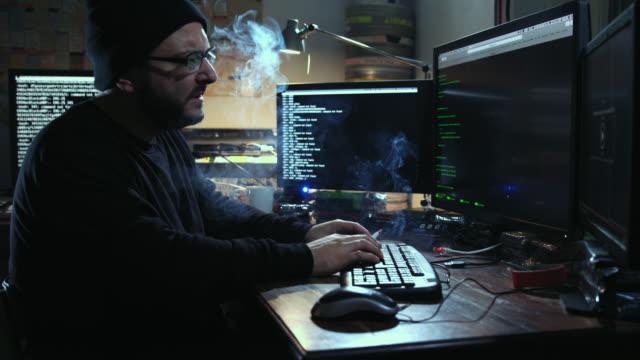 Digital threat by male cyber criminal computer hacker typing computer code while trying to break into a computer network during night – he smokes a cigarette.
